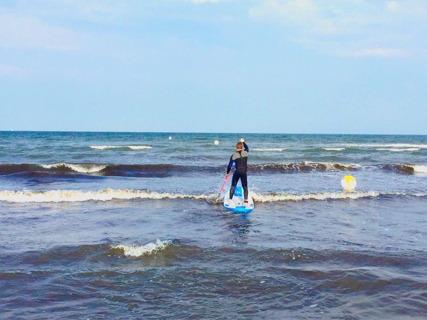 Mit dem SUP-Board in die Wellen der Ostsee: Im Herbst kann man mit etwas Glück sogar sein Paddel am Strand lassen und Wellen reiten. Foto: Luisa Praetorius