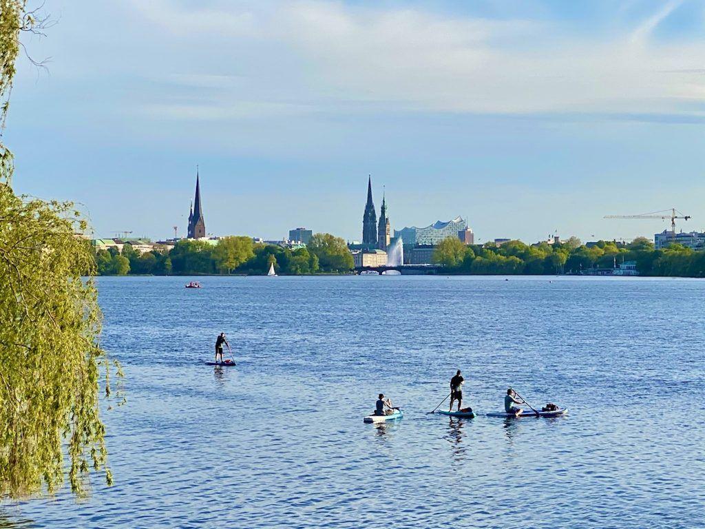Stehpaddler von dem typischen Hamburg Panorama: SUP auf der Alster ist im Sommer für Einwohner und Besucher ein spannender Zeitvertreib. Foto: Sascha Tegtmeyer